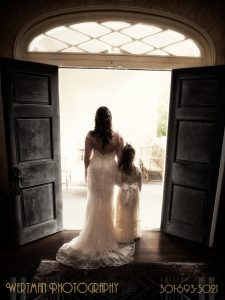 Bride and girl looking out doorway entrance