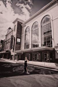 senior in front of theatre
